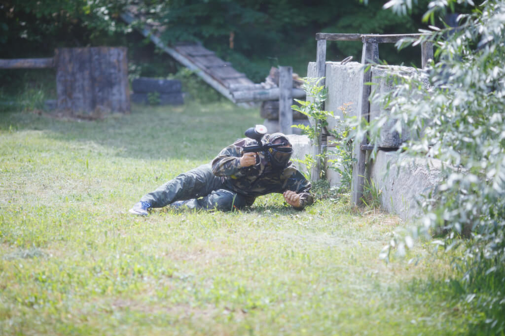 Paintball sport player in uniform and mask with gun outdoors.